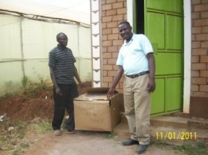 Two men standing next to a newly-arrived box of uniforms.